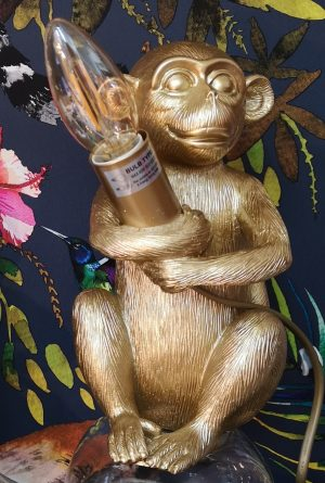A gold table lamp of a monkey holding a LED candle bulb