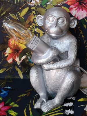 A silver table lamp of a monkey holding a LED candle bulb